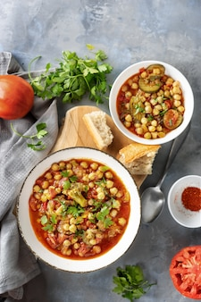 Vegan chickpeas stew with tomatoes on grey surface