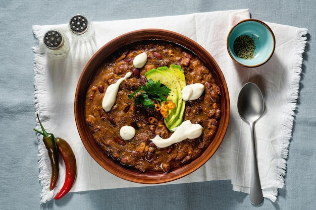 Vegan chili soup without meat, with pinto beans and avocado, served with yogurt made from soy on linen tablecloths. healthy eating