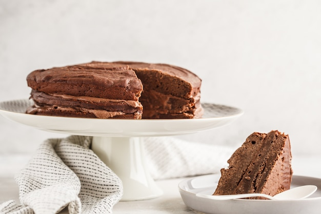 Vegan chocolate cake on a white dish for cake, copy space, light background.