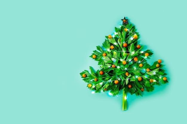 緑のセロリとライトと星で飾られたトマトで作られたビーガンのクリスマスツリー
