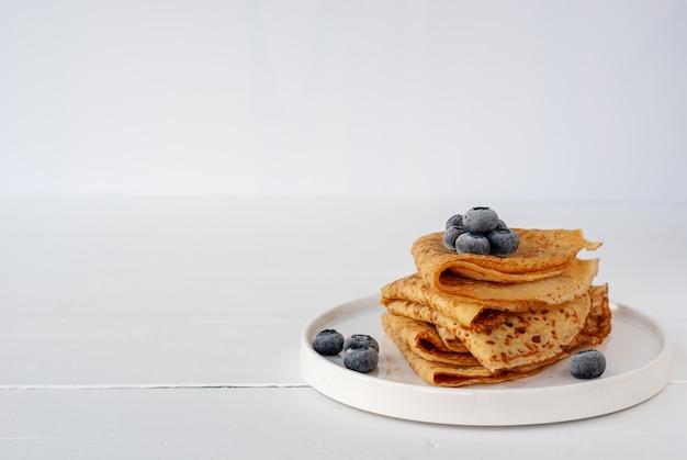 레시피 텍스트 복사 공간이있는 흰색 나무 테이블에 냉동 블루 베리와 함께 병아리 콩 가루, 알 목적 글루텐 프리 밀가루 및 귀리 우유로 만든 채식주의 자 크레페