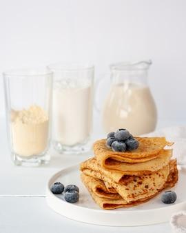 ひよこ豆粉、多目的グルテンフリー粉、オート麦ミルクから作られたビーガンクレープ、白い木製のテーブルに冷凍ブルーベリー