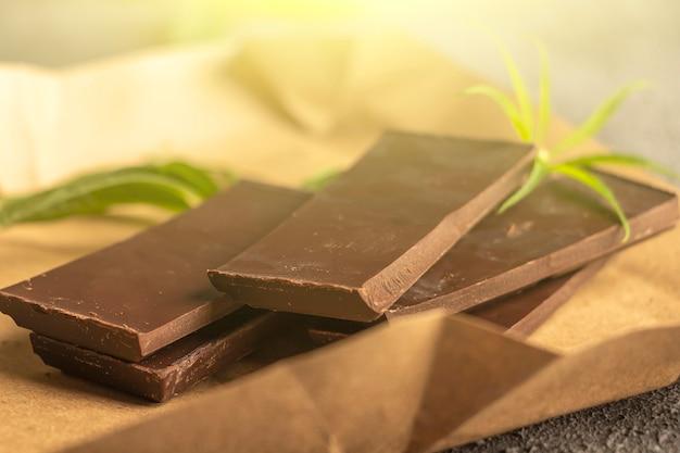 대마초 잎이 있는 비건 다크 초콜릿. cbd 버터가 있는 사막. 음식, 완전 채식주의 자, 보충제 개념의 약용 마리화나