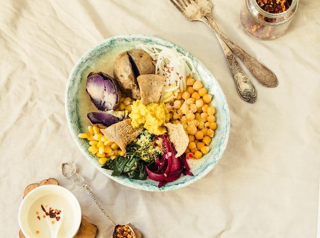 ビーガンデトックスランチ、紫芋、ほうれん草の煮込み、フムスとコーンクラッカー。