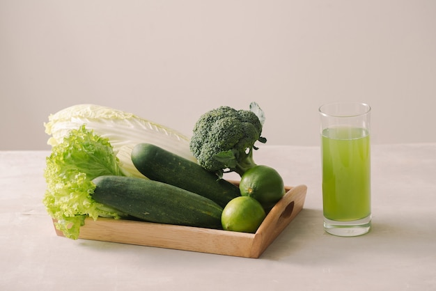 Vegan diet food. detox drinks. freshly squeezed juices and smoothies from vegetables, wooden tray, ingredients. copy space