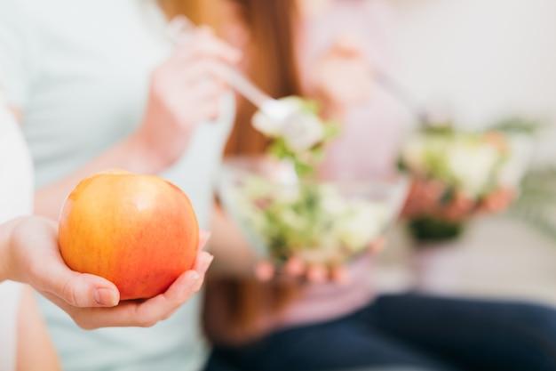 비건 채식. 건강한 영양 생활. 여성의 손에 애플 전채입니다. 샐러드 그릇을 가진 여자.
