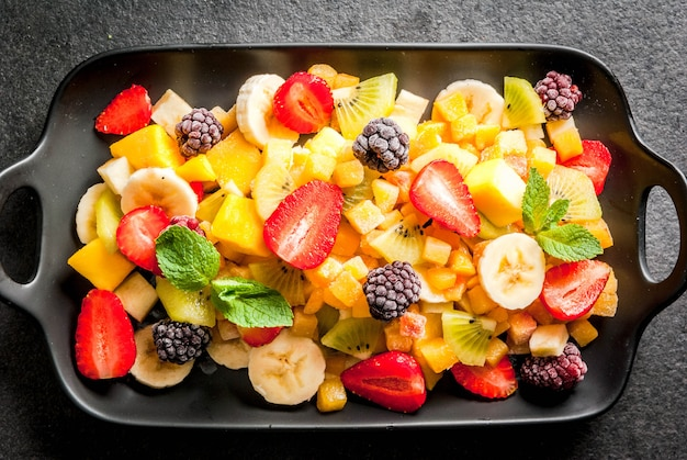 Vegan dietary foods. vitamins. dessert. summer. salad of fresh organic fruits mango, peach, apple, banana, kiwi, strawberry, blackberries. on black ceramic plate, black stone table top view copyspace