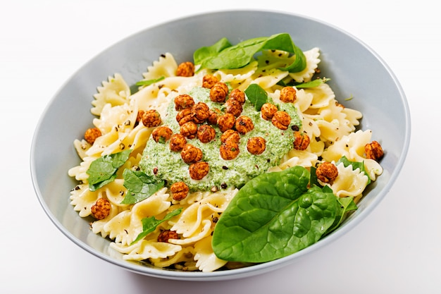 Vegan farfalle pasta with spinach sauce with fried chickpeas
