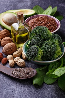 Vegan fat sources –  flax, spinach, broccoli, nuts, olive, oil and avocado. concept of healthy foo
