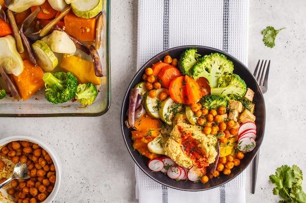 Vegan flat lay, buddha bowl with baked vegetables, chickpeas, hummus and tofu.