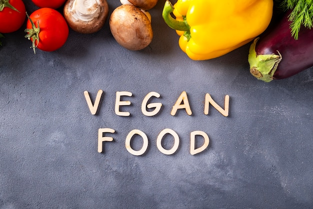 ビーガンフードの背景。灰色の背景と生の有機野菜に木製の文字で書かれた「ビーガンフード」という言葉。健康なビーガンダイエットの材料。上面図