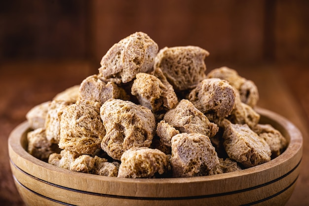 Вегетарианская пища, грубый соевый белок, также называемый соевым мясом, текстурированный кусочками в деревянной миске.