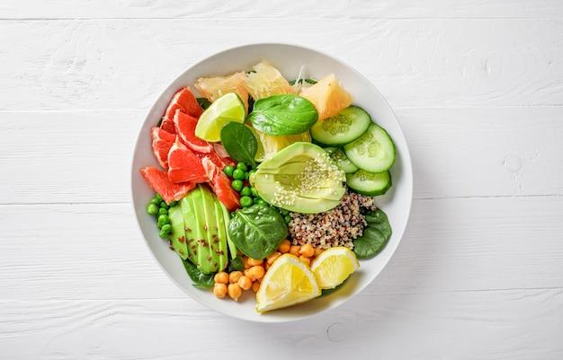 ビーガンフードのコンセプト:白い背景にアボカド、キュウリ、グリーンピース、ひよこ豆、ほうれん草、柑橘系の果物とキノア。上面図。