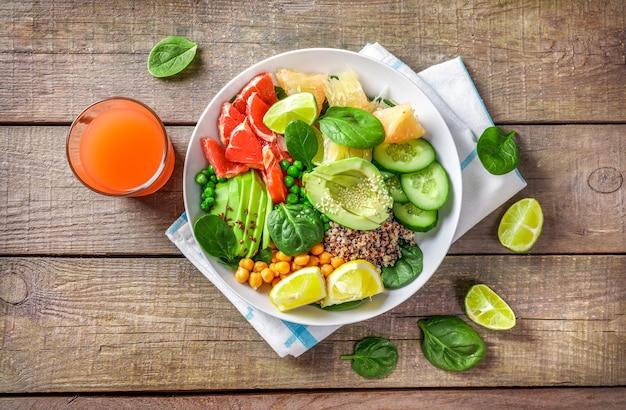 ビーガンフードのコンセプト:木製の背景にアボカド、キュウリ、グリーンピース、ひよこ豆、ほうれん草、柑橘系の果物とキノア。