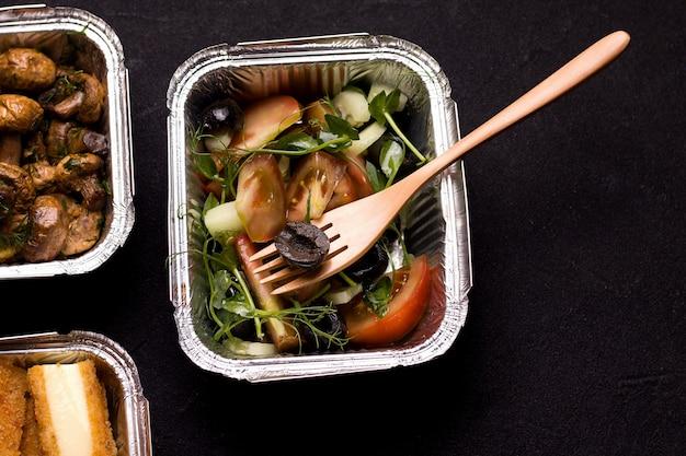 ビーガンフードデリバリーコンセプト。コンテナー内のオリーブ、トマト、マイクログリーンのサラダ