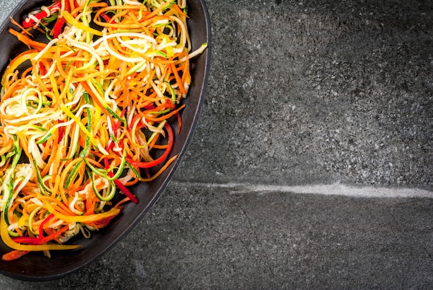 ビーガンフード、ダイエット。野菜麺、ニンジンのパスタ、ズッキーニ、ピーマン。石のテーブルで料理を焼く準備ができています。 copyspaceトップビュー