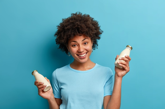 Vegan food and nutrition concept. cheerful dark skinned woman with curly hair holds bottle of fresh almond milk