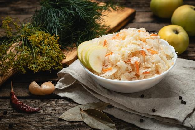 Vegan food - sauerkraut with apples on a wooden surface