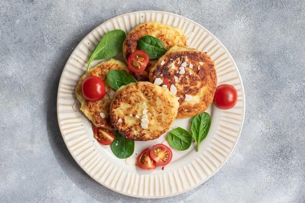 ビーガンフード。トマトとほうれん草のズッキーニのパンケーキ