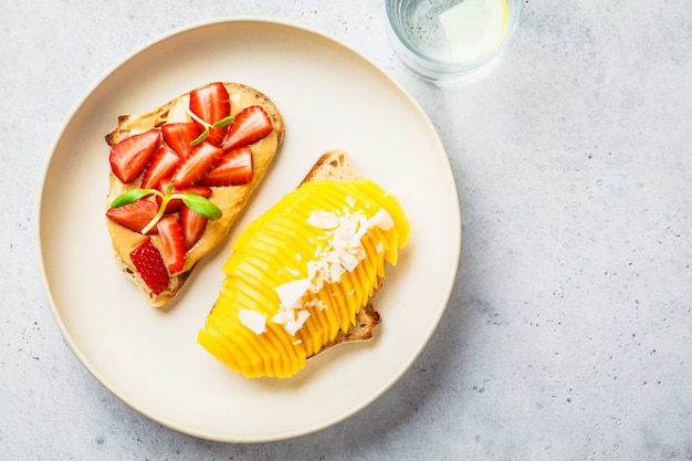 Vegan fruit sandwiches with mango, strawberry and peanut butter on white plate, top view.