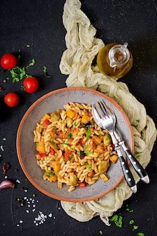 Овощная паста vegan fusilli с тыквой, брюссельской капустой, паприкой и морковью. вид сверху