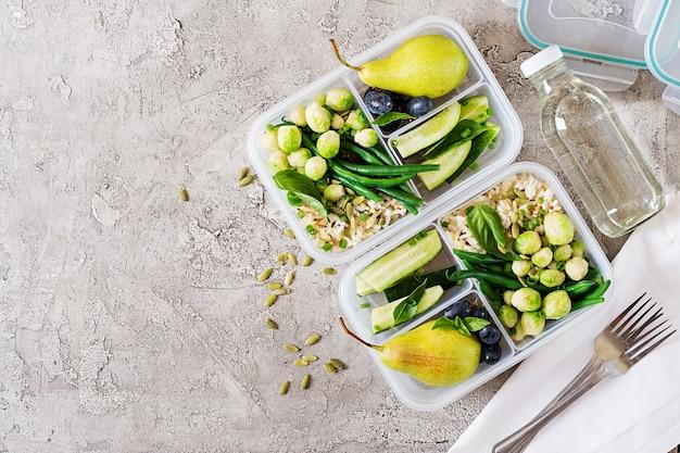 Веганские зеленые контейнеры для приготовления еды с рисом, зеленой фасолью, брюссельской капустой, огурцом и фруктами.