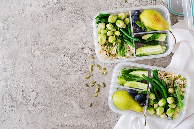 ご飯、インゲン、芽キャベツ、キュウリ、果物を含むビーガングリーンミールの準備容器。ランチボックスで夕食。