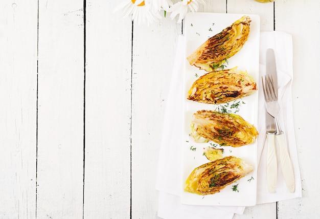 ビーガン焼きキャベツステーキ白の木製の背景に。健康食品。上面図。平置き