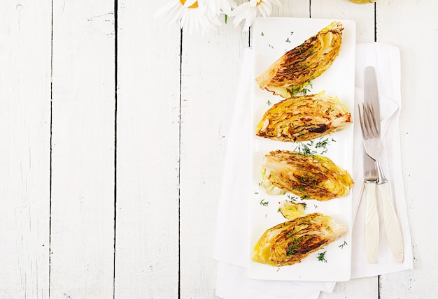 Vegan grilled cabbage steaks on white wooden background. healthy food. top view. flat lay