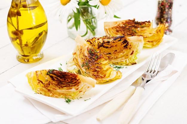 Bistecche di cavolo alla griglia vegan sul tavolo di legno bianco. cibo salutare.