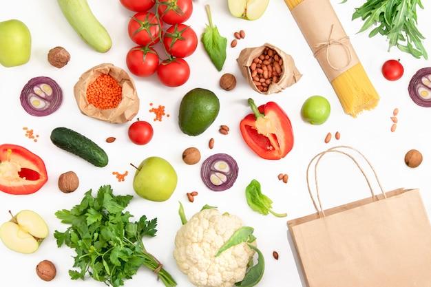 Веганский продуктовый набор органических овощей, фруктов и круп на белом с коричневой сумкой. торговая концепция.