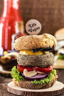 Vegan hamburger, with soy-based hamburger. wooden sign written in english: vegan life