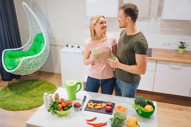 ビーガン幸せな愛情のあるカップルは、キッチンで生野菜を調理しながらデトックスドリンクを保持しています。
