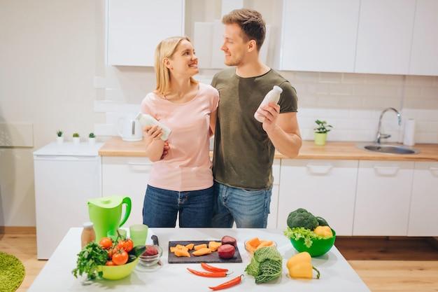 ビーガン幸せな愛情のあるカップルは、白いキッチンで生野菜を調理している間、自然なスムージーのボトルを保持しています。