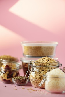Vegan health food over pink background with copy space. nuts, seeds, cereals, grains in glass jars.