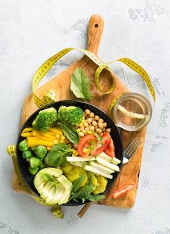 ビーガン健康的なバランスの取れた食事のコンセプトです。測定テープ付きベジタリアン仏ボウル。ヒヨコマメ、ブロッコリー、コショウ、トマト、ほうれん草、ルッコラ、アボカド、白い背景の上のプレート。上面図