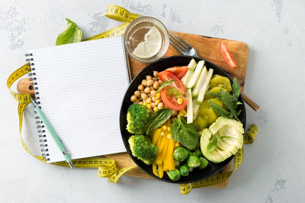 ビーガンの健康的なバランスの取れた食事。空白のノートブックと測定テープとベジタリアンの仏bowl。ヒヨコ豆、ブロッコリー、コショウ、トマト、ほうれん草、ルッコラ、アボカドのプレート。トップv