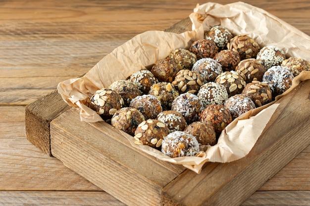 오트밀, 치아씨드, 코코넛 플레이크, 코코아, 말린 과일, 아몬드가 포함된 비건 건강 에너지 볼. 흰색 나무 상자에 쿡 에너지가 없습니다.