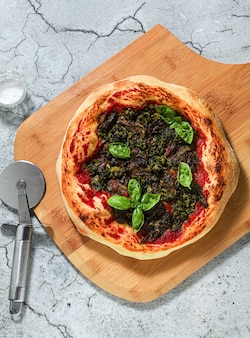 Vegan italian pizza with green vegetables and basil without cheese.