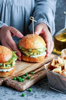 白い背景にサラダとヨーグルトソースを添えた、ウォマムの手にビーガンレンズ豆のハンバーガー。植物ベースの食品の概念。
