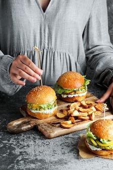 Веганские гамбургеры из чечевицы в руках womam, с салатом и йогуртовым соусом на белом фоне. концепция питания на основе растений.