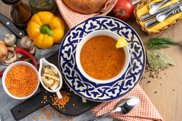 Vegan lentil soup with lemon and wheat chips in a plate with a traditional uzbek