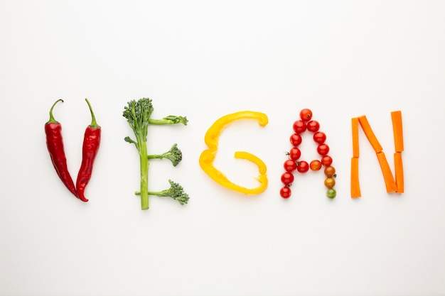 Vegan lettering made out of vegetables on white background