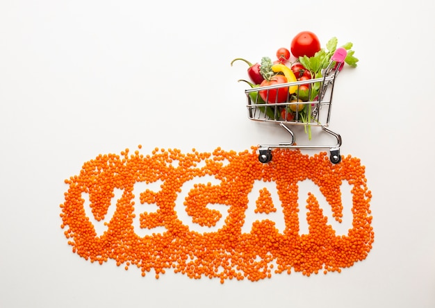 Vegan lettering with delicious vegetables in small shopping cart