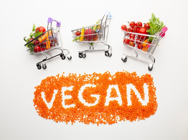 Vegan lettering with delicious vegetables in small shopping carts