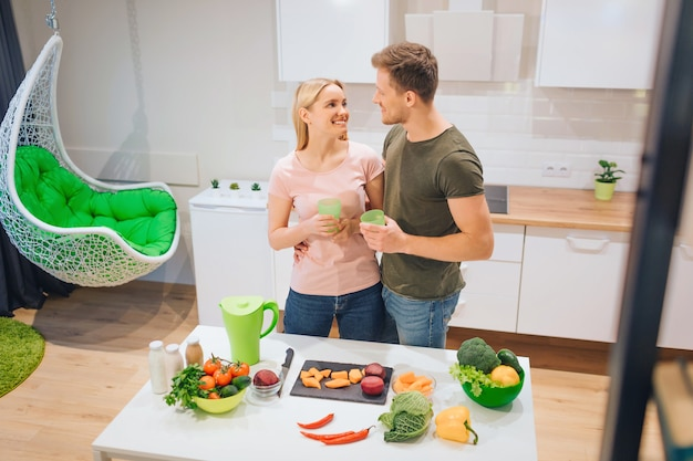 Vegan loving couple holds fresh detox drinks while cooking raw vegetables in the kitchen
