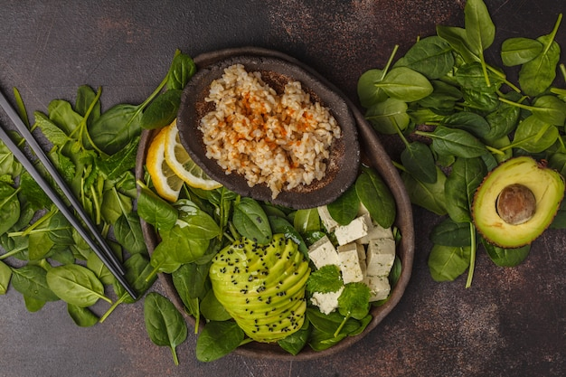 Vegan lunch with brown rice, avocado and tofu on a dark background, vegan food background, top view.
