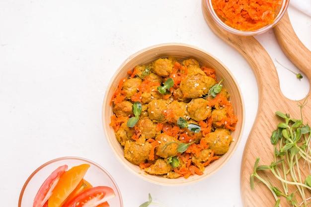 Веганский обед с соевым мясом, зеленью и овощами на белой тарелке. вид сверху. копировать пространство