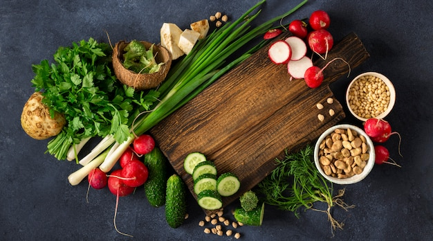 Vegan menu concept. wooden rustic cutting board with ingredients for cooking vegan food on dark background top view