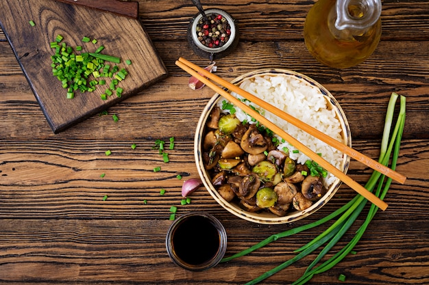 Vegan menu. dietary food. boiled rice with mushrooms and brussels sprouts in asian style. top view. flat lay.